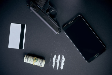 Mobile phone, powder drug like cocaine, gun, credit card and money on black table