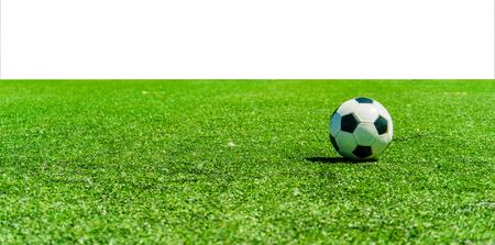Soccer ball on grass against white background