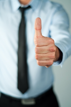 assert: young business man showing thumb up