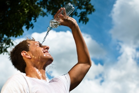 action fund: sportsman throwing water over his head for refreshment Stock Photo