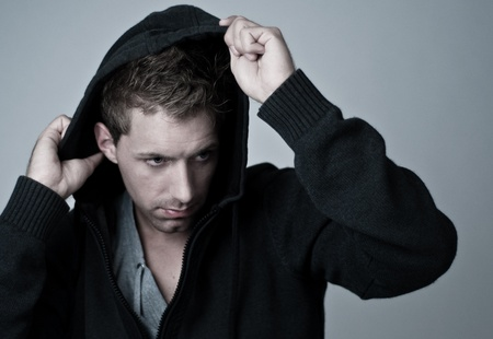 humanly: young man taking of his hood Stock Photo