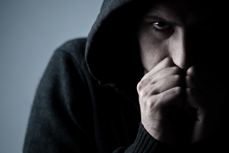 evil eyes: angry man wearing a hood Stock Photo