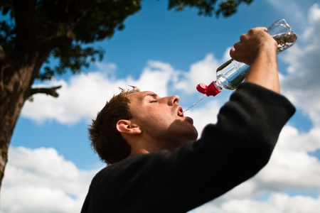 depletion: sportsman drinking water after training Stock Photo