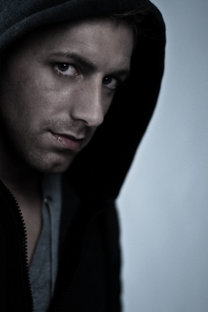 young man with intensive eyes wearing a hood  photo