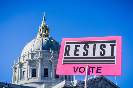 January 20, 2018 San Francisco  CA  USA - Resist vote sign raised at the Womens March rally which took place in the Civic Center Plaza; the City Hall building can be seen in the background