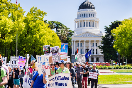 April 14, 2018 Sacramento  CA  USA - Participants to the March for Science and the Tax March walk on the Capitol Mall; California State Capitol building in the background