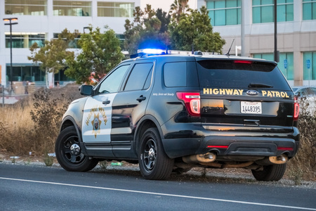 September 21, 2018 Santa Clara / CA / USA - Highway Patrol car stopped on the side of the freeway in the evening 免版税图像 - 112496910