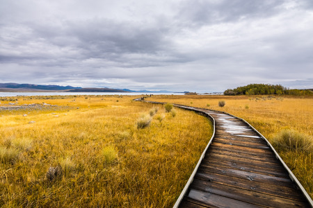 Wooden boardwalk in the Mono Lake Tufa State Natural Reserve on a cloudy autumn day, California Stock Photo