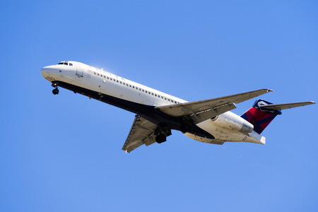 September 11, 2018 San Jose / CA / USA - Flying Delta Air Airlines aircraft approaching Norman Y. Mineta San Jose International Airport and preparing for landing; blue sky background Banque d'images - 112497377
