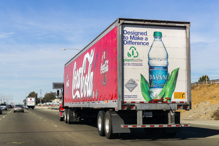 October 27, 2018 Fremont  CA  USA - Coca Cola truck driving on the freeway in East San Francisco Bay Area; Coca Cola logo printed on the side and Dasani Purified Water bottle displayed on the back