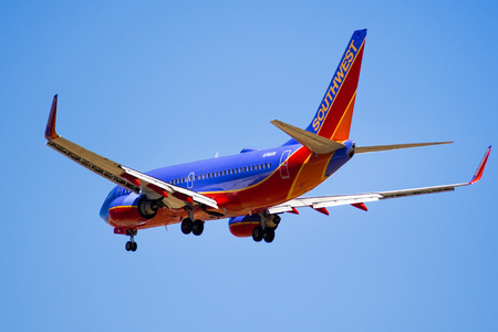 September 11, 2018 San Jose  CA  USA - Flying Southwest Airlines aircraft approaching Norman Y. Mineta San Jose International Airport and preparing for landing; blue sky background