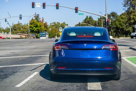 19 de octubre de 2018 Palo Alto / CA / EE. UU. - Tesla Model 3 se detuvo en un semáforo Editorial