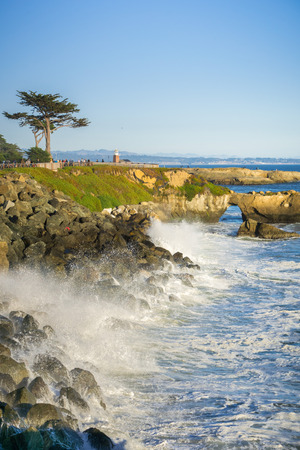 Waves crashing on the rocky shoreline of the Pacific Coast; Santa Cruz surfing museum in the background; California