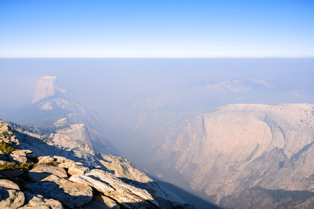 View towards Half Dome and the valley beyond on a day with low visibility due to the smoke coming from the Ferguson Fire, Yosemite National Park, California