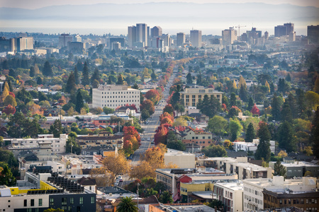 Aerial view of north Oakland on a sunny autumn evening; downtown Oakland in the background; buildings in UC Berkeley in the foreground; San Francisco bay, California