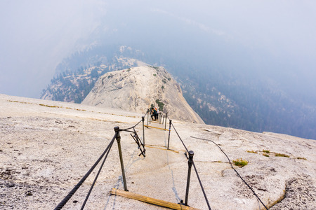 Looking down on the Half Dome cables on a summer day; smoke covering the sub dome and the valley beyond; Yosemite National Park, California