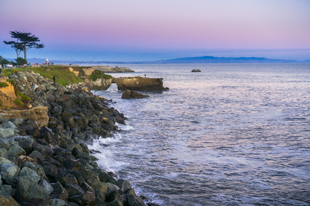 After sunset view of the rugged Pacific Ocean coastline, Santa Cruz, California; Santa Cruz surfing museum in the background Stock Photo