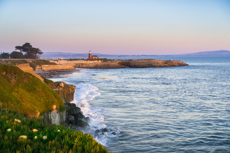 Sunset view of the Pacific Ocean rugged coastline, Santa Cruz, California; Santa Cruz surfing museum in the background