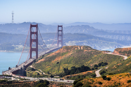 Aerial view of Golden Gate Bridge and the freeway bordered by the green hills of Marin Headlands on a sunny morning; San Francisco covered in a light fog layer in the background; California Reklamní fotografie
