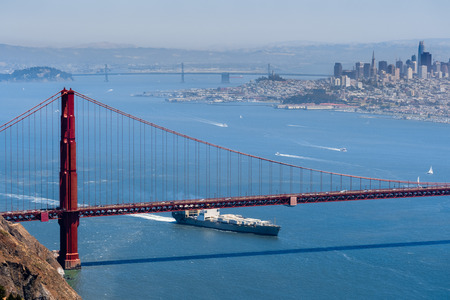 Cargo ship passing under Golden Gate Bridge on a sunny day; San Francisco skyline in the background; California Stock fotó
