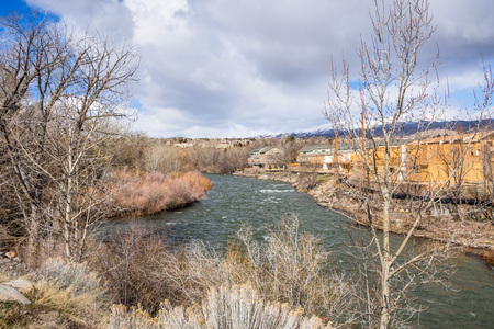 Truckee River flowing through a residential neighborhood in Reno, Nevada; snow covered mountains in the background Stock Photo