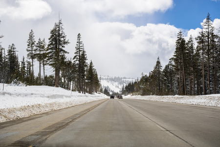 Cars driving on I80 interstate through the Sierra mountains close to lake Tahoe on a sunny winter day; the road has been cleared on snow, California