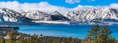 Vista panorámica hacia el lago Tahoe en un día claro soleado; la Sierra nevada al fondo; bosques de hoja perenne en primer plano