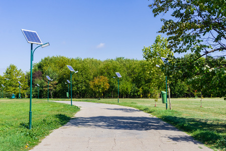 Park alley illuminated by solar powered street lights in Tineretului Park, Bucharest, Romania 版權商用圖片