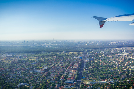 Taking off from Otopeni airport; flying over residential neighborhoods, Bucharest skyline in the background; Romania