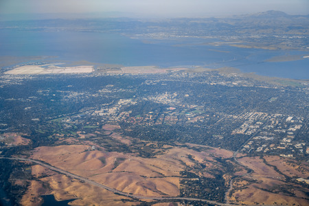 Aerial view of Silicon Valley towns (Palo Alto, Menlo Park, Redwood City); east bay and Mt Diablo in the background; San Francisco bay area, California