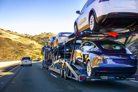 December 2, 2018 Gilroy  CA  USA - Car transporter carries Tesla Model 3 new vehicles along the highway, back view of the trailer