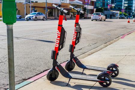 3 dicembre 2018 Los Angeles/CA/U.S.A. - i motorini elettrici di salto hanno parcheggiato su un marciapiede; JUMP è un sistema di condivisione dockless di biciclette e scooter elettrici acquisito da UBER; opera negli Stati Uniti e in Germania