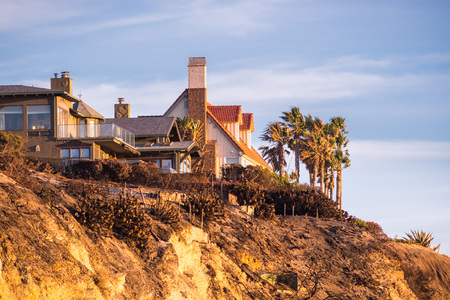 Sunset view of mansions built on top of cliffs on the Pacific Ocean coast, Malibu, Los Angeles county, California Stock Photo