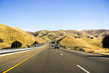 Driving through the golden hills of California in the San Luis Reservoir State Recreation area on a sunny morning Stock Photo