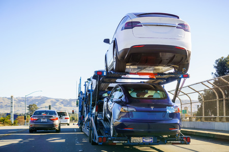December 2, 2018 Gilroy / CA / USA - Car transporter carries Tesla Model 3 new vehicles along the highway, back view of the trailer Reklamní fotografie - 113517546