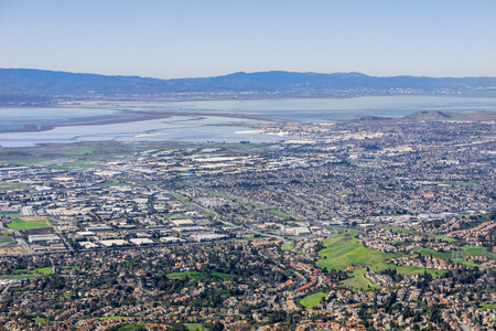 Aerial view of Fremont and Newark on the shoreline of east San Francisco bay area; Dumbarton bridge in the background; Silicon Valley, California