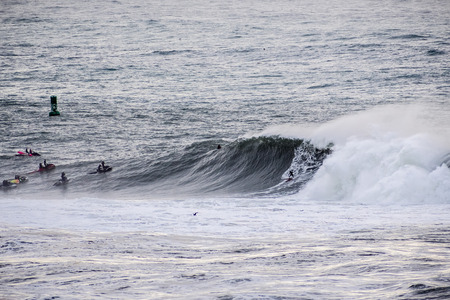 Surfers riding huge waves on the west coast, close to Pillar Point and Mavericks Beach, Half Moon Bay, California