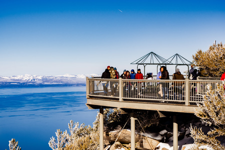 December 26, 2018 South Lake Tahoe  CA  USA - People admiring the scenery from the Heavenly Gondola Observation Deck; blue sky and Lake Tahoe visible in the background Stock Photo