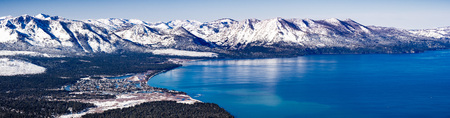Aerial view of Lake Tahoe on a sunny winter day, Sierra mountains covered in snow visible in the background, California