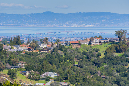 Residential neighborhood on the hills of San Francisco peninsula, Silicon Valley, San Mateo bridge in the background, California