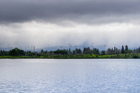 Shoreline lake on a cloudy day, rain pouring in the background, Mountain View, San Francisco bay area, California