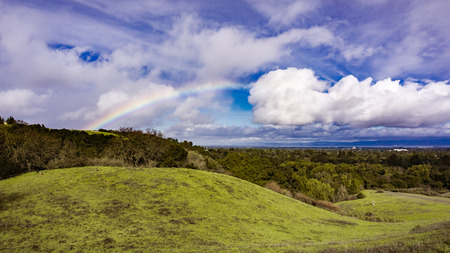 Panoramic landscape view of rainbow after a light rain and deer resting on the hills of Rancho San Antonio county park, south San Francisco bay, California