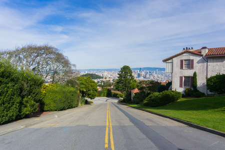 Two way street in the residential area of San Francisco; downtown views in the background, California