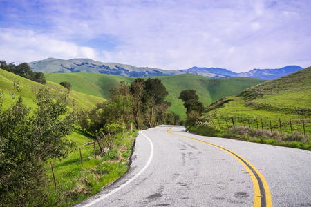 Paved road going through verdant hills, Mount Hamilton in the background, south San Francisco bay, San Jose, California 免版税图像