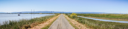 Panoramic view of levee going through the marsh and ponds in south San Francisco bay, California
