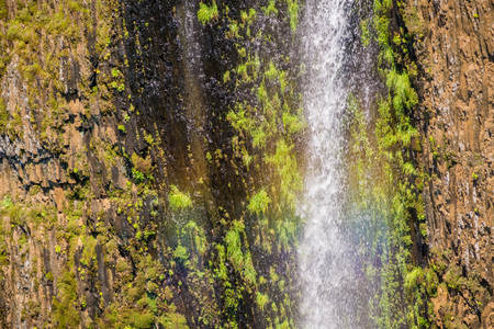 Rainbow created by the water of Phantom Waterfall dropping off over vertical basalt walls, North Table Mountain Ecological Reserve, Oroville, California