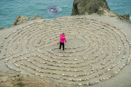 Girl playing in a rock maze on the Pacific Ocean coastline, San Francisco, California Stock Photo