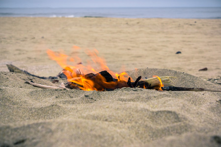 Small fire made using driftwood on the Pacific Ocean coastline, California Imagens