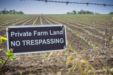 Private Farm Land No Trespassing sign posted on a barbed wire fence, California Stock Photo