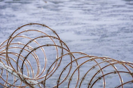 Razor barbed wire security fence, muddy marsh background Stock Photo